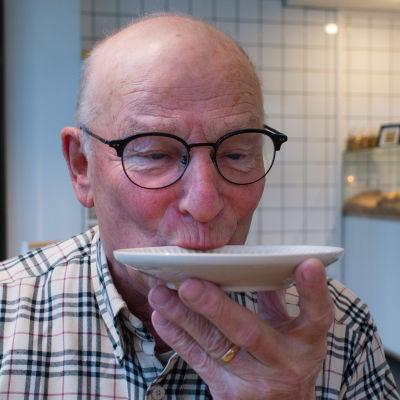 En äldre man dricker kaffe på fat