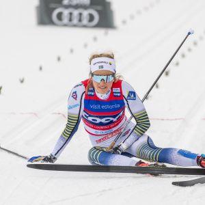 Stina Nilsson sitter på vid spåret utmattad efter målgång.