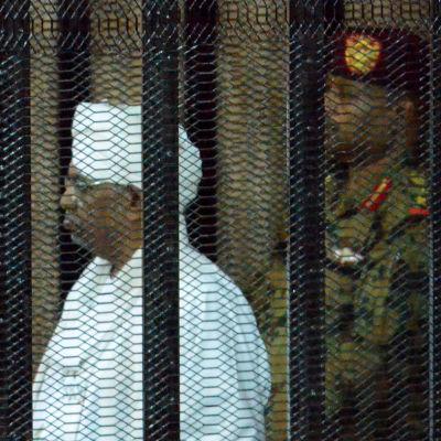 Sudans ex-president och en soldat står i den åtalades bur i en rättegång.