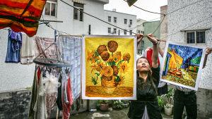 flicka i Kina hänger upp kopia av van Goghs solrosor