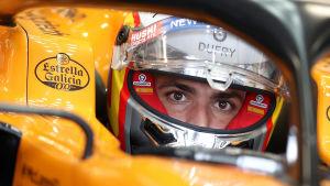 Carlos Sainz sitter i sin McLaren med visiret upp.