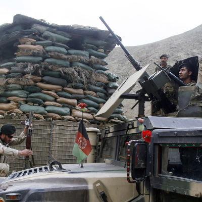 Tungt beväpnade afghanska soldater vid en bepansrad bil i norra Afghanistan.
