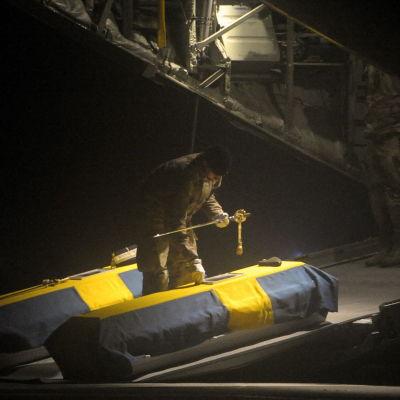 Kistorna till kapten Johan Palmloev och löjtnant Gunnar Andersson är täckta av svenska flaggor då de förs hem från Afghanistan.