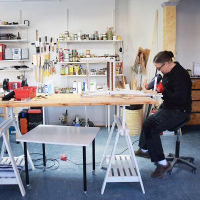 En bild på en kvinna som restaurerar en stol på ett bord. i bakgrunden syns burkar och redskap