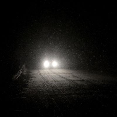 En bil närmar sig på snöig väg i bäcmörker.