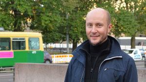 Tomas Palmgren står framför Mannerheimvägen med spårvagn och bilar i bakgrunden.