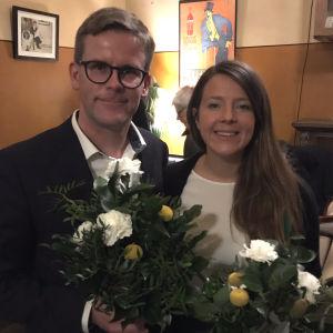Markus Blomquist och ida schauman står intill varandra med blommor i händerna.