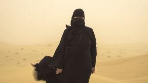 Hissa Hilal står ute i öknen under en sandstorm.
