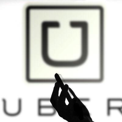 I förgrunden en person i profil som tittar på sin smarttelefon, i bakgrunden Ubers logotyp på en vägg.