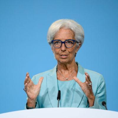 Christine Lagarde i turkos dräkt bakom ett vitt podium.