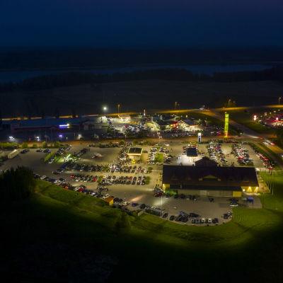 Flygbild över servicestation i Karis där hundratals bilar samlades en lördagsnatt i maj.