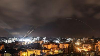 Två ljusspår från raketer syns mot en mörk himmel över en stad