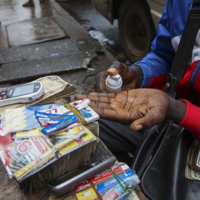 En gatuförsäljare i Liberia descinficerar sina händer.