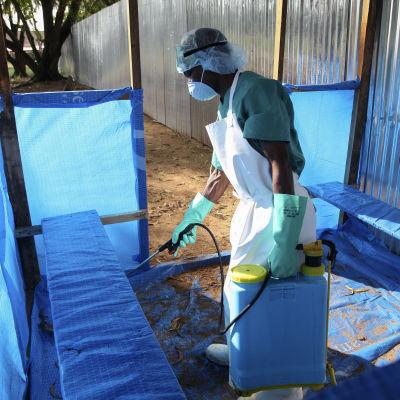 Liberiansk sjukskötare desinficerar väntutrymmen utanför en vårdenhet i Monrovia.