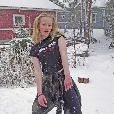 Elin står på gården utanför sitt hus