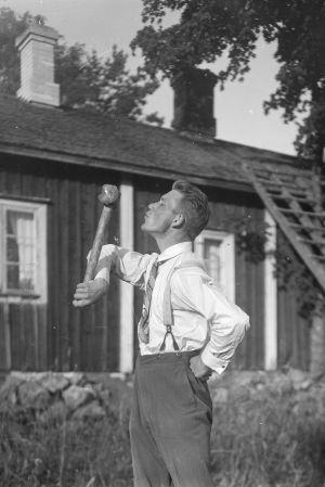 """En man leker leken """"kyssa gudfar"""", där han lyfter en slägga med en arm och kysser släggan. Bilden är tagen 1930 i Bromarf."""