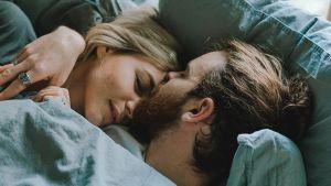 Pariskunta makaa sängyllä, mies pussaa naista.