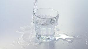 Vatten som rinner ner i ett glas. En del av vattnet rinner över och bildar pölar.