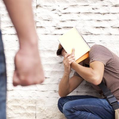 en man sitter tryckt mot en vägg, en annan står med knuten näve och tittar