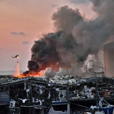 Vyn visar förstörda byggnader brand i hamnen efter explosionen i Beirut. Rök stiger upp från huset och en helikopter som deltar i släckningsarbetena flyger förbi.