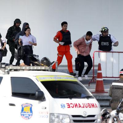 Poliisit avustavat ihmisiä ulos rakennuksesta.