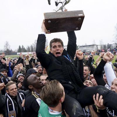 Simo Valakari nostaa mestaruuspokaalia joukkueen ympäröimänä.