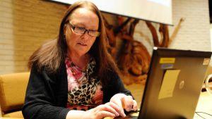 Läkare Ulla Slama sitter vid dator i samband med föreläsning