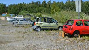 Två övergivna bilar bredvid båttrailrar.