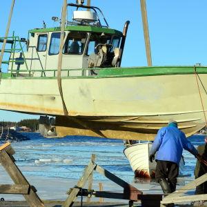 En fiskebåt hänger i kranbilens remmar