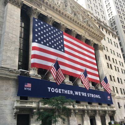 """""""Yhdessä olemme vahvoja""""-teksti ja suuri Yhdysvaltain lippu rakennuksen seinässä."""