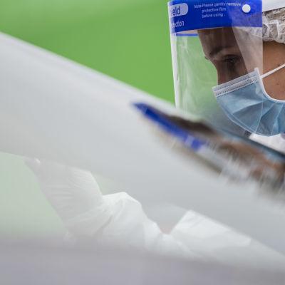 En sjukvårdare i skyddsutrustning utför coronatest på person i bil.