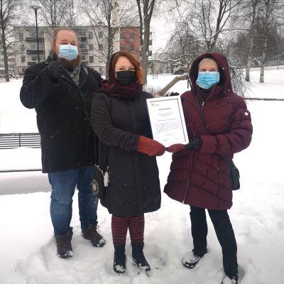 Vammaisneuvoston puheenjohtaja luovuttaa kunniakirjan Riihimäen kaupungille.