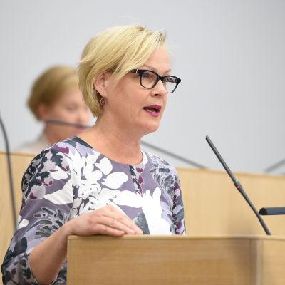 Eva Biaudet står vid riksdagens talarstol och håller ett anförande.
