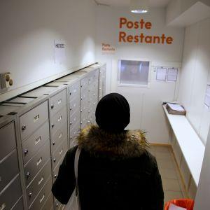 man hämtar posten ur poste restante-fack.