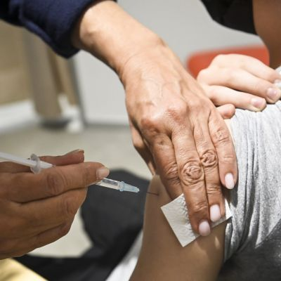 Vaccin injiceras i en persons överarm.