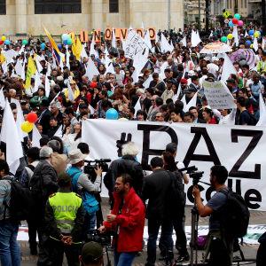 Demonstranter som stöder fredsprocessen håller upp ett stort plakat med ordet fred under en demonstration i Bogota.