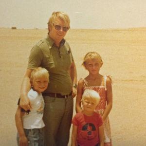 Vaaleahiuksinen mies kolmen vaalea hiuksisen lapsen kanssa aavikolla.