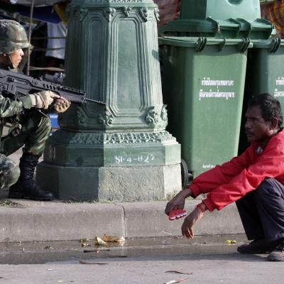 En soldat och en demonstrant som är på regeringens sida i Thailand.