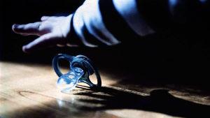Pienen lapsen käsi haparoi tuttia lattialta. Kuva elokuvasta Jail Lullaby.