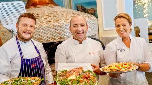 Tre pizzabagare med färdigt gjorda pizzor ler mot kameran.