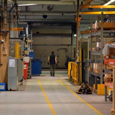 Anställd går längs korridoren i en stor hall i metallföretaget Mapromec.