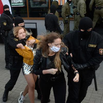 Naamioidut poliisit pitävät otteessaan nuoria naisia.