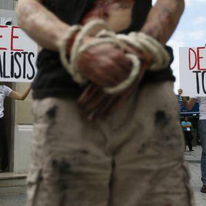 händer förbundnda med skyltar i bakgrunden som uppmanar att avsluta tortyr och mördandet av journalister