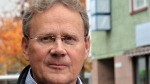 En ansiktsbild på en medelålders man som tittar i kameran. Det är Karisbon Stefan Mutanen, tidigare vd för Folkhälsan.