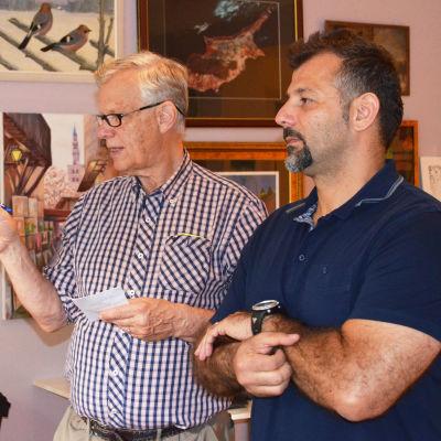 Hagelstam och Adham står framför vägg med tavlor, diskuterar fundersamt.