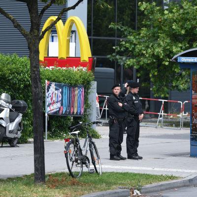 Poliser står utanför köpcentret Olympia och en McDonald's-logo i München den 23 juli 2016.