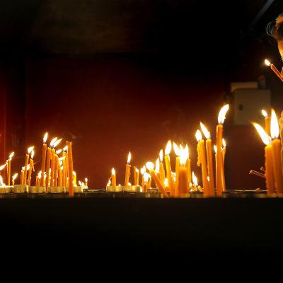 Människor lägger ner ljus vid minnesmärket för dem som dog udner revolutionen i Timisoara.
