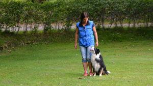 Kvinna står bredvid hund.