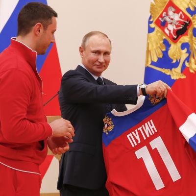 Vladimir Putin tilldelas ryska ishockeytröjan av Ilja Kovaltjuk inför OS 2018.