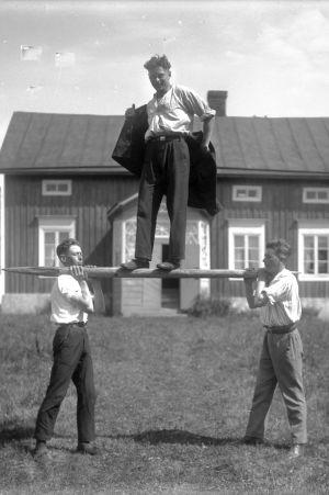 En man balanserar på en stång som bärs av två män. Bilden är tagen 1930 i Jomala, Åland.